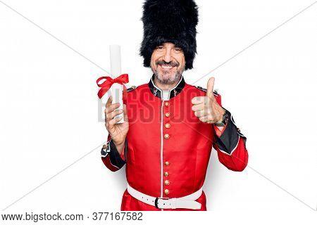 Middle age handsome wales guard man wearing traditional uniform holding diploma degree smiling happy and positive, thumb up doing excellent and approval sign