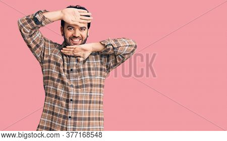 Young hispanic man wearing casual clothes smiling cheerful playing peek a boo with hands showing face. surprised and exited