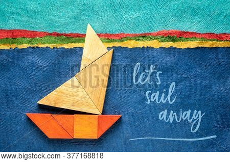 let's sail away inspirational note with a sailing boat built from seven tangram wooden pieces over a landscape created with handmade textured bark paper, travel and vacation concept