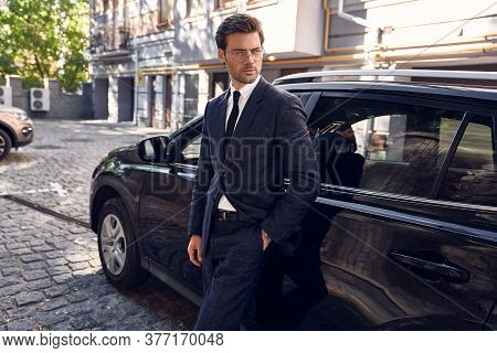 Side View Of Confident Business Man In Formalwear And Eyewear Leaning At The Car And Looking At Away