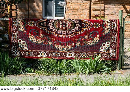 An Oriental Red Carpet With Patterns Dries On A Metal Fence Near The House. Carpet Cleaning And Dryi