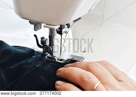 Sewing Process.  Seamstress Hands At Work, Threads And Needles. Woman Hands Using The Sewing Machine