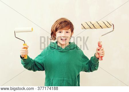 Cute Boy With Painting Roller. Home Renovation Concept. Son Helps Parents To Paint Wall. Boy Paints