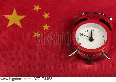 Peoples Republic Of China Flag And Vintage Alarm Clock Close Up. Time To Learn Chinese.