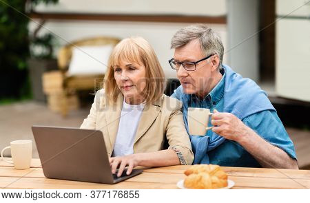 Senior Married Couple Watching Movie Together On Laptop Near Rv At Campground, Panorama
