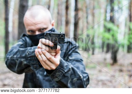 A Man In Dark Military Clothes And A Mask Is Aiming From A Weapon In The Forest, Close-up