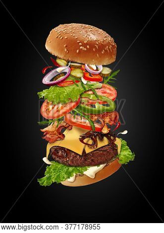 Maxi Burger With Flying Ingredients Against Black Background. Ham, Beef Cutlet, Cheese, Mayonnaise,