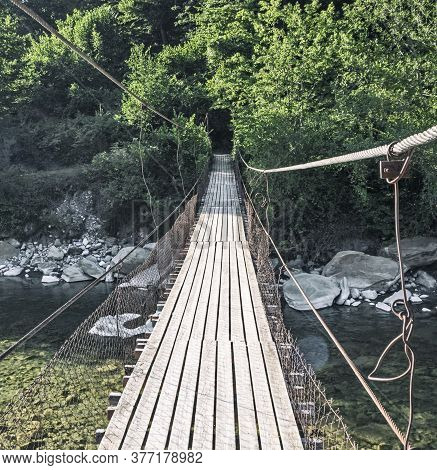 Hanging Bridge With Wooden Planks Over River Water
