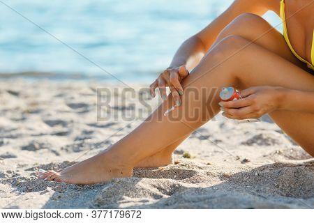Safe Sunbathing. Unrecognizable Woman Applying Sun Cream On Smooth Tanned Legs Sitting On Beach On S