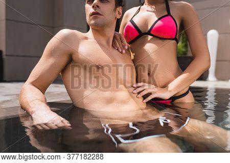 Cropped View Of Woman In Swimwear Touching Man In Swimming Pool