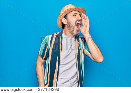 Middle age handsome tourist man on vacation wearing shirt and hat over blue background shouting and screaming loud to side with hand on mouth. Communication concept.