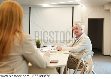 Portrait Of White-haired Senior Businessman Sitting At Table In Conference Room And Listening To Fem