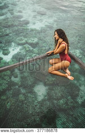 Beautiful Tanned Woman In Red Swimsuit Relaxing In Over-reef Hammock With Amazing View Of Coral Reef