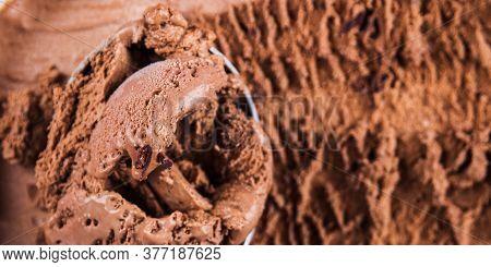 Full Ice Cream Scoop In Chocolate Ice Cream Tub. Macro Texture Banner