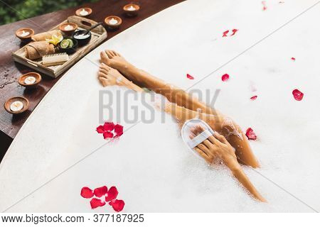 Woman Washing Legs In Bath Tub With Foam Bubbles And Use Natural Loofah Sponge. Spa Treatment, Body