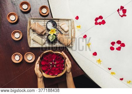 Woman Hands Holding Wooden Bowl With Red Rose Flower Petals. Romantic Spa Set With Lime, Scrub, Salt