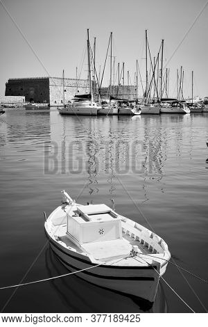 Small fishing boat in the harbour near Koules Fortress in Heraklion, Crete, Greece. Greek scenery, black and white photography