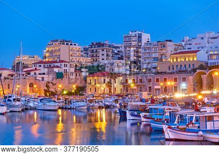 View of Heraklion city with harbour with yachts and fishing boats at dusk, Crete island, Greece. Greek scenery
