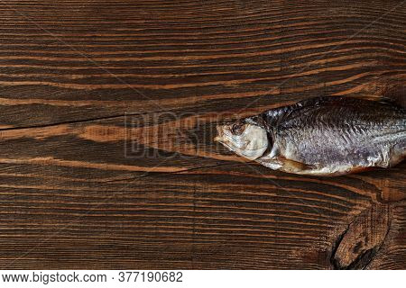 One Dried Or Jerky Salted Roach, Tasty Clipfish On Wooden Background. Salty Beer Appetizer. Traditio