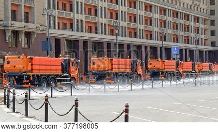 Column Of Municipal Watering Machines Washes Asphalt Of City Streets In The Morning.urban Public Uti