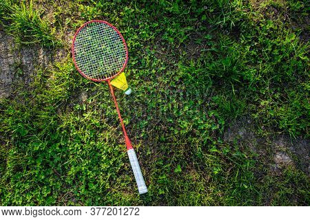 Badminton Racket With A Shuttlecock On The Green Grass, Summer Active Games. Copy Space