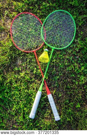 Two Badminton Rackets With A Yellow Shuttlecock On The Green Grass, Summer Active Games. Vertical Ph
