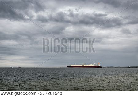 Lng Tanker In Seaport - Rainy Dramatic Clouds On The Ship And Gas Terminal