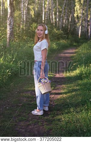 Beautiful Middle Age Woman Walking In The Forest With Flower Basket. Summer Evening Walking. Back Vi