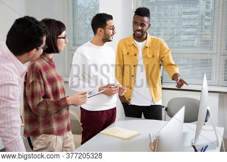 Multy-ethnic group of creative business people standing at the office desk and working with computer