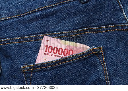 Banknote Money One Hundred Thousand Indonesia Rupiah In The Back Pocket Of Blue Jeans. Concept Of Sa