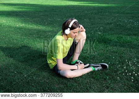 Handsome Teenager Boy Listening To The Music In Headphones. Outdoors Summer Time. Teen Boy Wearing Y