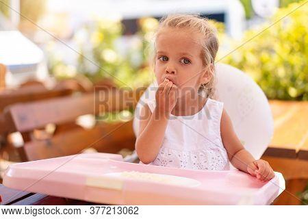 Cute Little Caucasian Girl Eating Spaghetti At Table Sitting In Child Seat Outdoor Restaurant. Healt