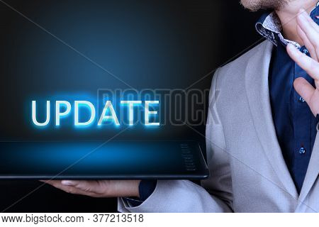 Businessman, Man Holds In His Hand A Tablet With A Neon Word, Update Text. Business Concept.