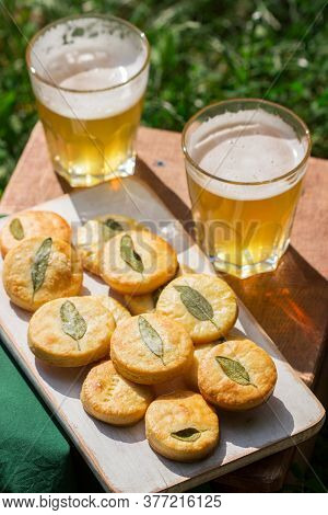 Salty Shortbread Cookies With Sage And Beer On A Wooden Stool.