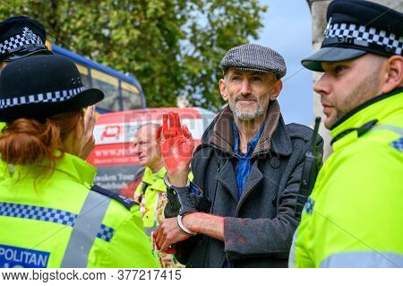 London - October 18, 2019: Handcuffed Male Extinction Rebellion Protester With Red Painted Hand Surr