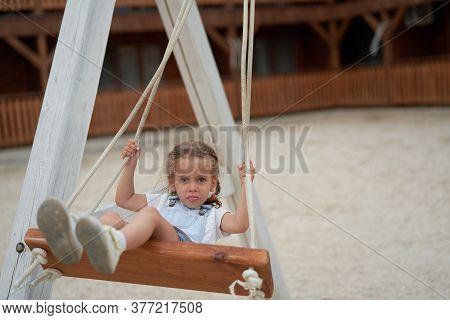 Playful Kid Swinging Swing. Joyful Little Girl Play Having Fun Playground Summertime Enjoyment Outsi