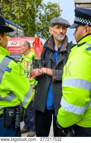 London - October 18, 2019: Vertical Shot Of Handcuffed Male Extinction Rebellion Protester With Red
