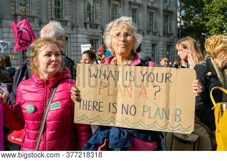 London - October 18, 2019: Middle Aged Female Extinction Rebellion Protester Holds A What Is Your Pl