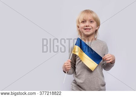 Young Smiling Fair-haired Boy Holding Flag Of Ukraine On White Background. Study Of Ukrainian.