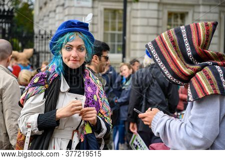 London - October 18, 2019: Vibrantly Dressed Extinction Rebellion Protester Looks Directly At The Ca