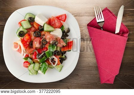 Greek Salad On Brown Wooden Background . Greek Salad On White Plate With Fork And Knife Top View . H