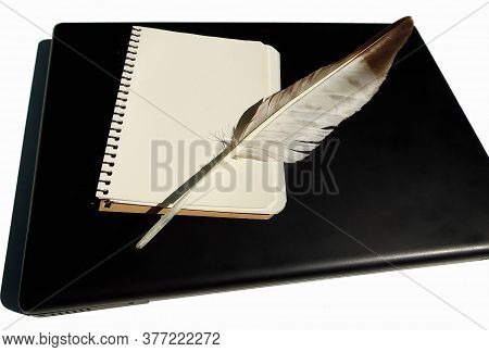 A Blank Loose-leaf Notebook And A Bird Of Prey Feather Lie On A Laptop On An Isolated White Backgrou