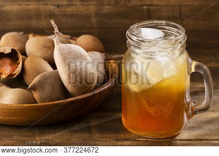 Delicious Sweet Drink, Tamarind Juice And Ice On A Rustic Wooden Table - Tamarindus Indica