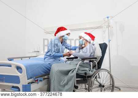 Christmas Day Isolated In Hospital Room With Coronavirus, Nurse Take Comfort Elderly Woman Celebrati