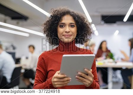 Portrait of happy multiethnic businesswoman using digital tablet in agency. Successful business woman in casual clothing working on tablet. Mixed race young woman looking at camera in creative office.