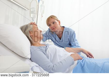 Nurse Take Comfort Elderly Woman Lying In The Hospital Room Bed, By Stroking Her And Holding The Arm