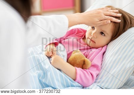 healthcare, medicine and people concept - close up of doctor measuring temperature of little sick girl lying in bed at home