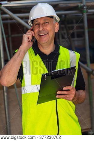 Male builder foreman, worker, contractor or architect on construction site holding black clipboard and talking on his cell phone