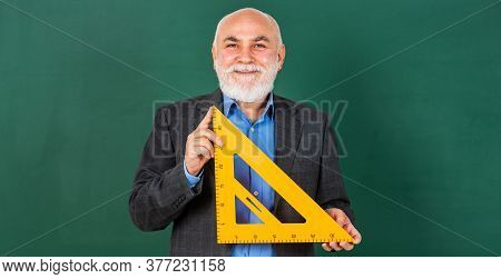 Senior Man Teacher Use Math Triangle Tool. Bearded Tutor Man At Blackboard. Back To School. Math Sci