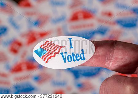 Finger With I Voted Button In Front Of Many Voting Stickers Given To Us Voters In Presidential Elect